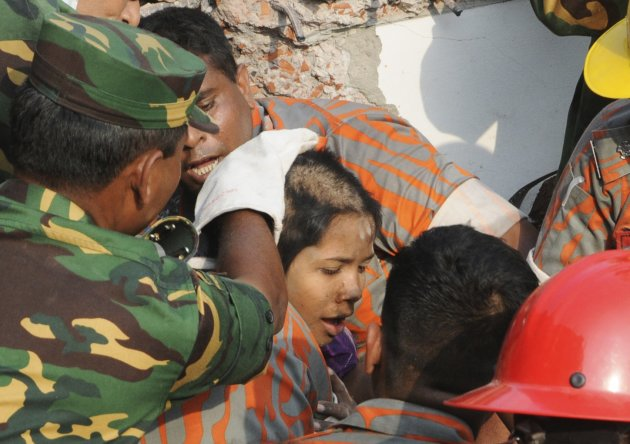 Rescue workers rescue a woman from the rubble of the collapsed Rana Plaza building, in Savar May 10, 2013. The woman, identified by local media only as Reshma, was rescued on Friday after spending 17 days trapped under the rubble of a Bangladesh factory building that collapsed on April 24, killing more than 1,000 people, police and military officials said. REUTERS/Sanaul Huq   (BANGLADESH - Tags: DISASTER TPX IMAGES OF THE DAY)