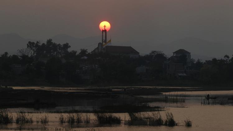 The sun sets past a Catholic church in Vietnam's northern Ninh Binh province