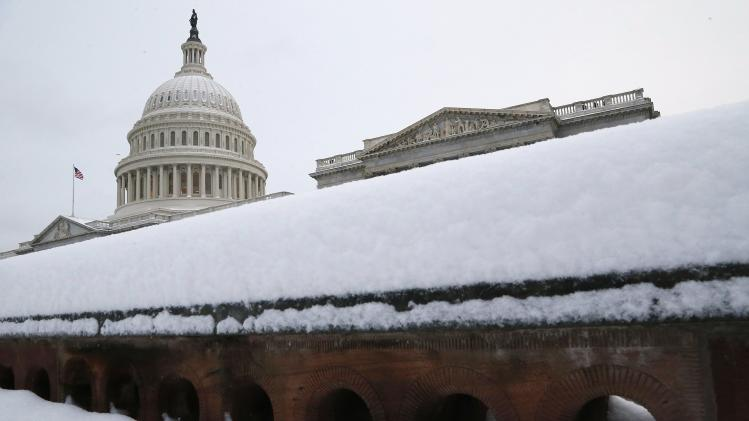 Several inches of fresh snow cover a low wall at the U.S. Capitol in Washington