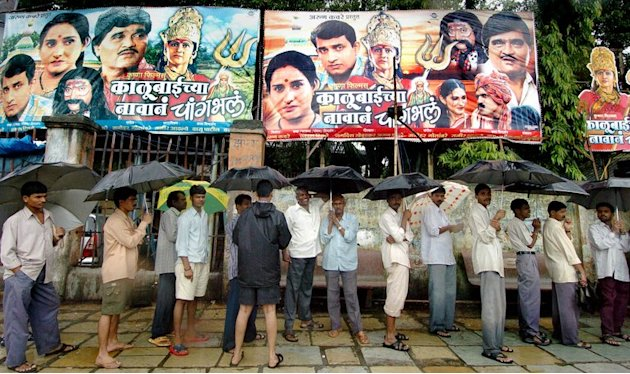 Indian movie buffs queue up in the rain outside a cinema theatre in Mumbai on August 1, 2005