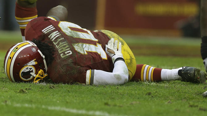 Washington Redskins quarterback Robert Griffin III touches his back after a sack by Baltimore Ravens defensive end Arthur Jones during the second half of an NFL football game in Landover, Md., Sunday, Dec. 9, 2012. (AP Photo/Alex Brandon)