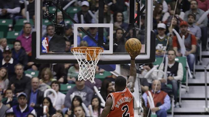 Chicago Bulls' Nate Robinson (2) shoots as Utah Jazz's Al Jefferson, left, and teammate Paul Millsap (24) look on in the third quarter during an NBA basketball game Friday, Feb. 8, 2013, in Salt Lake City. The Bulls defeated the Jazz 93-89. (AP Photo/Rick Bowmer)