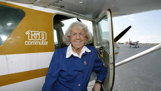 """FILE - In this March 7, 2005 file photo, Evelyn """"Mama Bird"""" Johnson, 95, poses by a plane at Moore-Murrell Airport in Morristown, Tenn. Johnson, the pioneering female pilot and Guinness world record holder has died. She was 102. The Farrar Funeral Home in Jefferson City, Tenn., said she died Thursday, May 10. Johnson held the Guinness Book of World Records certificate for most hours in the air for a female pilot. (AP Photo/Wade Payne, File)"""
