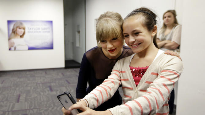 Taylor Swift poses for a photo with Piper Moralez, 11, at the Country Music Hall of Fame and Museum on Saturday, Oct. 12, 2013, in Nashville, Tenn. Swift is at the facility to open the $4 million Taylor Swift Education Center. (AP Photo/Mark Humphrey)