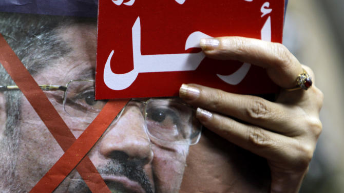 "An Egyptian protester holds anti-President Mohammed Morsi poster and a red card with Arabic word ""Leave"" during a protest in Cairo, Egypt, Saturday, June 29, 2013. Thousands of supporters and opponents of the embattled Islamist president held rival sit-ins in separate parts of Cairo Saturday on the eve of opposition-led mass protests aimed at forcing Mohammed Morsi from power. (AP Photo/ Amr Nabil)"