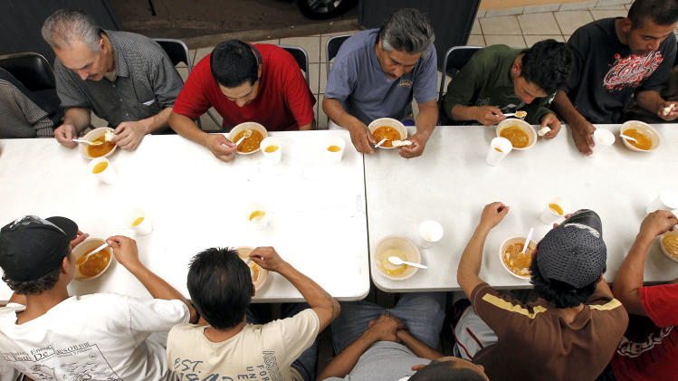 Dozens of men, many of them Mexican citizens, eat a modest dinner at a well known immigrant shelter, as many are making tough decisions on whether to try their luck at trying to make it to the United States, by illegally crossing the border, Thursday, Aug. 9, 2012, in Nogales, Mexico.  The U.S. government has halted flights home for Mexicans caught entering the country illegally in the deadly summer heat of Arizona's deserts, a money-saving move that ends a seven-year experiment that cost taxpayers nearly $100 million.(AP Photo/Ross D. Franklin)