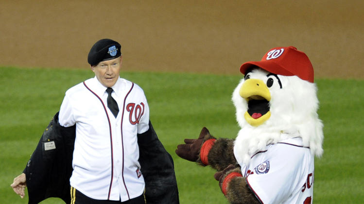 Gen. Martin Dempsey, left, chairman of the Joint Chiefs of Staff, removes his uniform to reveal a Washington Nationals jersey before throwing out the first pitch before Game 5 of the National League division baseball series between the Nationals and the St. Louis Cardinals on Friday, Oct. 12, 2012, in Washington. (AP Photo/Pablo Martinez Monsivais)