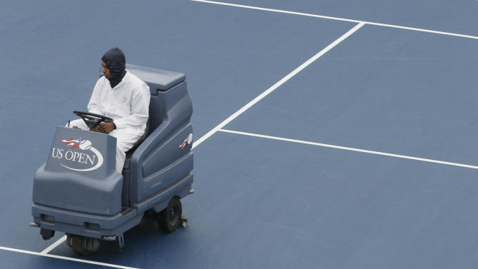 Tennis fans wait while the court at Arthur Ashe Stadium is dried during a rain delay at the U.S. Open tennis tournament in New York, Wednesday, Sept. 7, 2011. (AP Photo/Charlie Riedel)