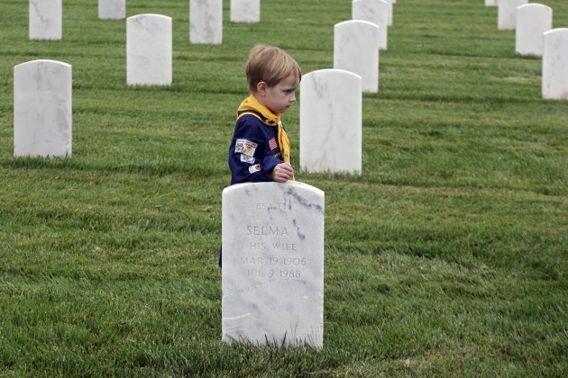 Cub Scout pauses at gravesite of U.S. military veteran at Los Angeles National Cemetery during a flag placement event to commemorate Memorial Day weekend in Los Angeles