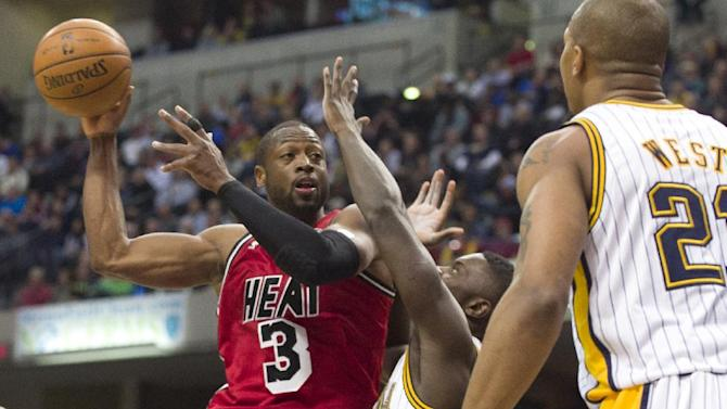 Miami Heat's Dwyane Wade (3) looks for a teammate under the basket as he is defended by Indiana Pacers' Lance Stephenson, center, during the first half of an NBA basketball game in Indianapolis, Friday, Feb. 1, 2013. (AP Photo/Doug McSchooler)