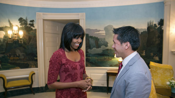 In this image released by the White House, first lady Michelle Obama greets David Hall, one of eight citizen co-chairs for the Inauguration, in the Diplomatic Reception Room of the White House in Washington, Thursday, Jan. 17, 2013. The photo is showing something different about Obama - bangs in her hair. (AP Photo/The White House, Lawrence Jackson)