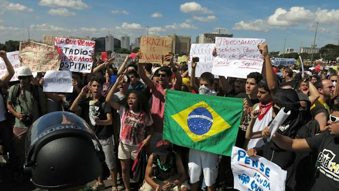 """Demonstrators protest in front of the National Stadium, some holding signs that read in Portuguese; """"We don't want stadiums, we want more hospitals,' and """"We don't need stadiums, we need education, health and security,"""" before of the opening soccer match of the Confederations Cup between Brazil and Japan, in Brasilia, Brazil, Saturday, June 15, 2013. The protesters are complaining that too much money was spent for the World Cup while the local population continues to struggle. (AP Photo/Tales Azzoni)"""