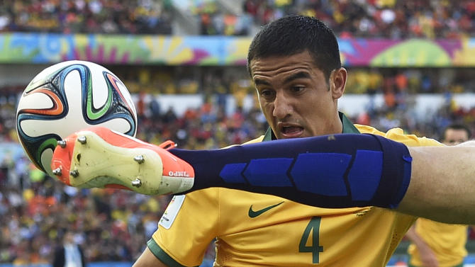 Australia's Tim Cahill, left, watches as Netherlands' Ron Vlaar clears the ball during the group B World Cup soccer match between Australia and the Netherlands at the Estadio Beira-Rio in Porto Alegre, Brazil, Wednesday, June 18, 2014. (AP Photo/Martin Meissner)