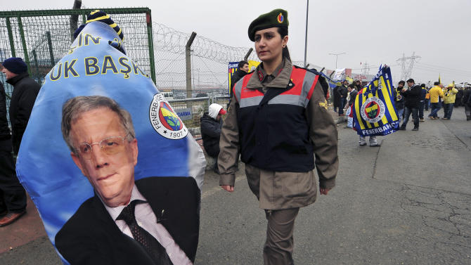 "FILE - In this Tuesday, Feb. 14, 2012 file photo a paramilitary police officer walks past a poster of Aziz Yildirim as thousands of Fenerbahce fans shout slogans outside a Turkish court house in support of 93 suspects, including the club's jailed president Aziz Yildirim, ahead of the opening hearing of a match-fixing case in Silivri near Istanbul, Turkey. Yildirim, 60-year-old tycoon was convicted in July of ""forming and leading a criminal gang"" that rigged four games and offered payments to players or rival club officials to fix three others _ all so Fenerbahce could stay in the Champions League, a benefit the club estimated to be worth $58.5 million a year. He is appealing his conviction, maintaining his innocence. (AP Photo)"
