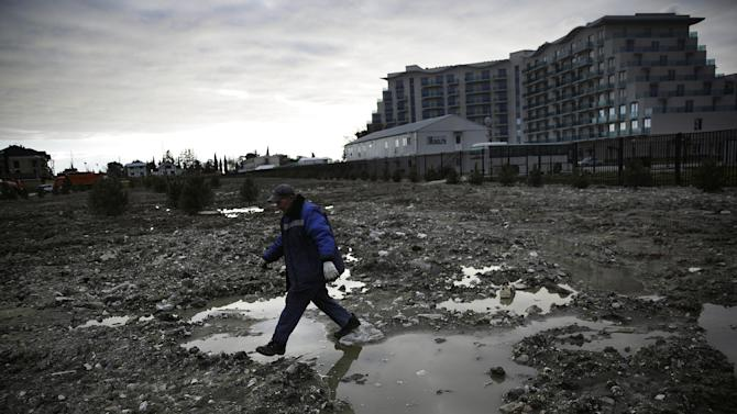 A construction worker steps over a puddle in a lot being prepared to be turned into a grassy lawn next to a newly built hotel across from the Olympic Park at the 2014 Winter Olympics, Thursday, Feb. 6, 2014, in Sochi, Russia