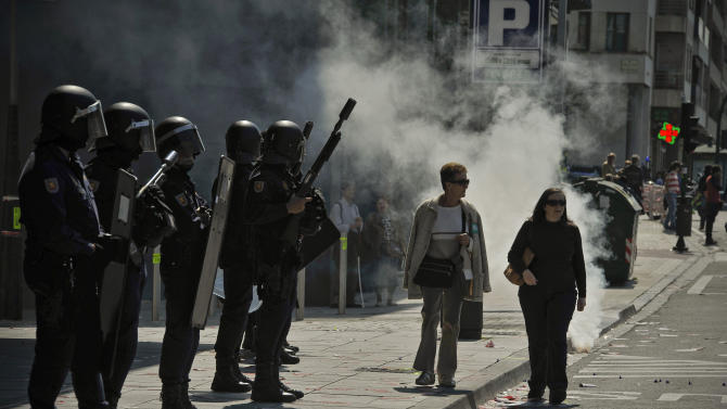 Riot police officers stands on the street as people walk past them during the general strike to protest against the government's tough new labor reforms and cutbacks in Pamplona, northern Spain, Thursday, March 29, 2012. Flag-waving Spanish workers livid over labor market reforms they see as flagrantly pro-business blocked traffic Thursday, formed boisterous picket lines outside wholesale markets and bus garages as part of a nationwide general strike against the new conservative government. (AP Photo/Alvaro Barrientos)