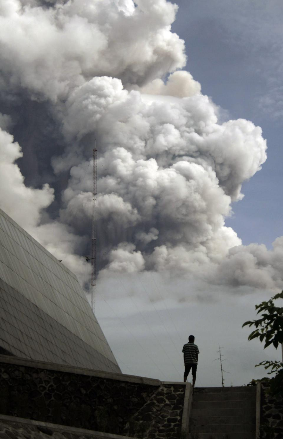 An Indonesian man watches as Mount Merapi erupts in Hargobinangun, Yogyakarta, Indonesia, Wednesday, Nov. 3, 2010. Indonesia's most dangerous volcano is once again sending searing gas clouds and burning rocks down its scorched flanks. (AP Photo/Slamet Riyadi)