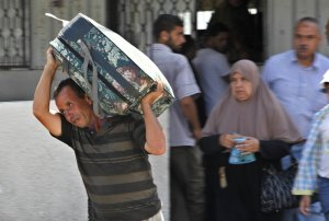 A Palestinian man carries a luggage to the bus at the …