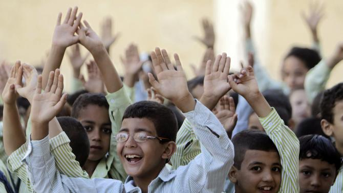 Students raise their hands on the first day of their new school year at a government school in Giza