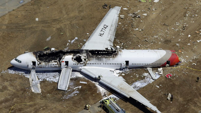 FILE - In this July 6, 2013 aerial file photo, the wreckage of Asiana Flight 214 lies on the ground after it crashed at the San Francisco International Airport in San Francisco. Asiana Airlines has been penalized $500,000 for failing to assist family members of passengers on the flight that crashed last year at San Francisco airport, federal transportation officials said Tuesday, Feb. 25, 2014. (AP Photo/Marcio Jose Sanchez, File)