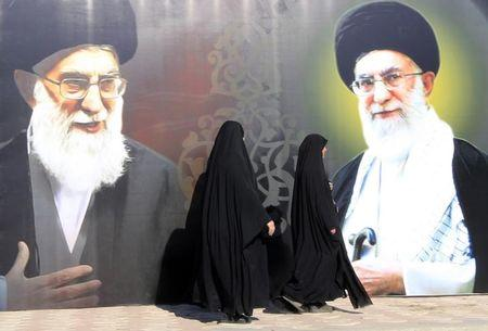 Iraqi women walk past a poster depicting images of Shi'ite Iran's Supreme Leader Ayatollah Ali Khamenei at al-Firdous Square in Baghdad