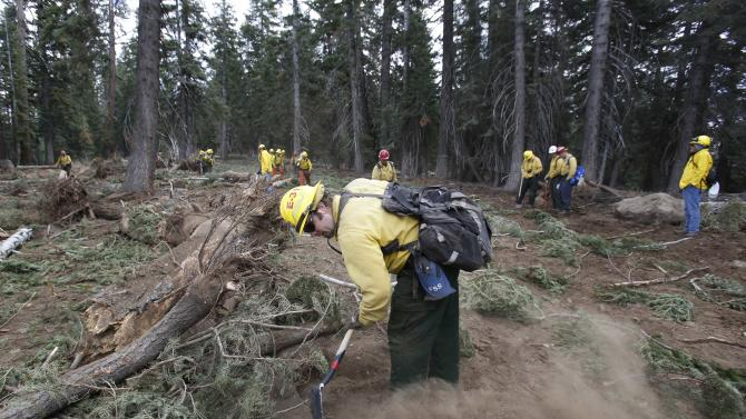 FILE - In this Sept. 25, 2013 file photo, Scott Small, and other National Forest Service crew members work to restore terrain that was bulldozed for a firebreak in the battle against Rim Fire on a nordic ski trail along Dodge Ridge in the Stanislaus National Forest, near Tuolumne City, Calif. The Forest Service says it will release a final decision Wednesday, Aug. 27, 2014, on how much timber to log from the Sierra Nevada's largest wildfire in recorded history. Last year's Rim Fire burned 400 square miles including parts of Yosemite. A debate has since raged about sending burned and dead trees to lumber mills or leave them and let nature take its course. (AP Photo/Rich Pedroncelli, File)