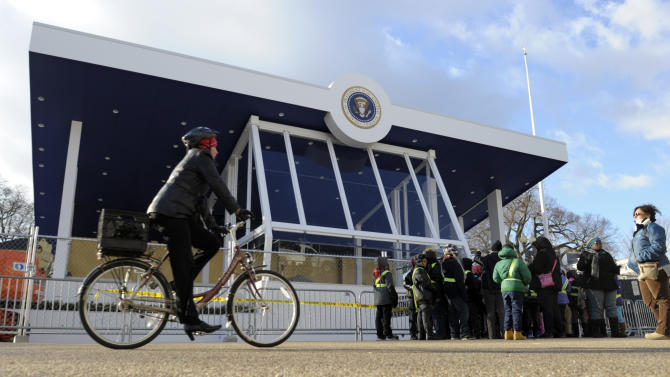 """A cyclist prepares to pass visitors standing in front of the Inaugural Parade Reviewing Stand outside the White House on Pennsylvania Avenue in Washington, Friday, Jan. 18, 2013, in preparation for this weekend's 57th Presidential Inauguration"""" where President Barack Obama will be sworn in for a second term.  (AP Photo/Susan Walsh)"""