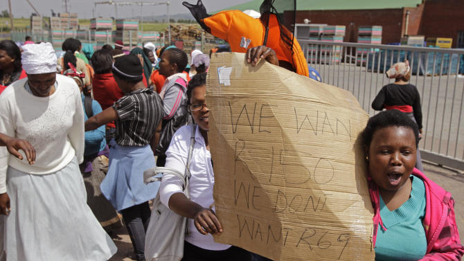 A protesting farm worker, right, holds a banner banner reading 'We want 150 rand ($13) we don't want 69 rand ($8)' per day wages as she and others protest in the town of Stellenbosch, South Africa, Thursday, Nov. 15, 2012. Farm workers angered over their minimum daily wages launched a second day of violent protests in the nation's Western Cape, setting fires and marching through the countryside. (AP Photo/Schalk van Zuydam)