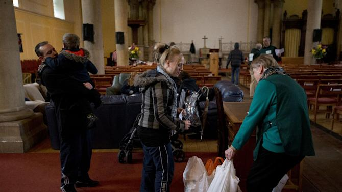 "In this photo taken Friday, April 5, 2013, a volunteer, right, gives bags of food to Natalie Cribbin, center, at a food bank in St Luke's Church in the West Norwood area of London. It's possible that official figures on first quarter economic growth, to be released Thursday, could put the country back in recession. It would take the smallest statistical variation to put the figure in negative territory which would place the country in recession, another recession _ the third since the 2008 financial crisis _ and is already being referred to with foreboding in the media as a ""Triple Dip"". (AP Photo/Matt Dunham)"