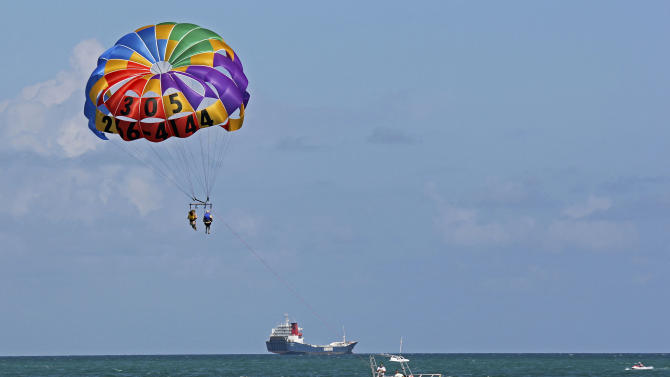 In this Sept. 24, 2012 photo, two people parasail over the Miami Beach,Fla. area. Soaring high above the ocean off South Beach, tethered only by a rope to a boat hundreds of feet below, riding in a parasail is at once exhilarating and oddly peaceful, even quiet. For millions of people, that's the takeaway from a once-in-a-lifetime experience. But every year there are accidents, some of them fatal. The Parasail Safety Council, which tracks injuries and deaths from the activity nationwide, reports more than 70 people have been killed and at least 1,600 injured between 1982 and 2012, out of an estimated 150 million parasail rides during those 30 years. Despite the inherent risk, few federal or state safety regulations exist for parasailing. In Florida, which has by far the largest number of parasail operators at about 120, repeated efforts to enact new rules following fatal accidents have landed with a thud. Florida is seen by safety proponents as a national bellwether because of parasailing's popularity in the state. (AP Photo/Tony Winton)