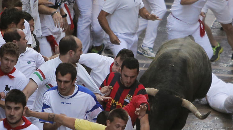 Revelers and an Adolfo Martin fighting bull run during the running of the bulls at the San Fermin festival, in Pamplona, Spain, Sunday, July 13, 2014. Revelers from around the world arrive to Pamplona every year to take part in some of the eight days of the running of the bulls. (AP Photo/Andres Kudacki)