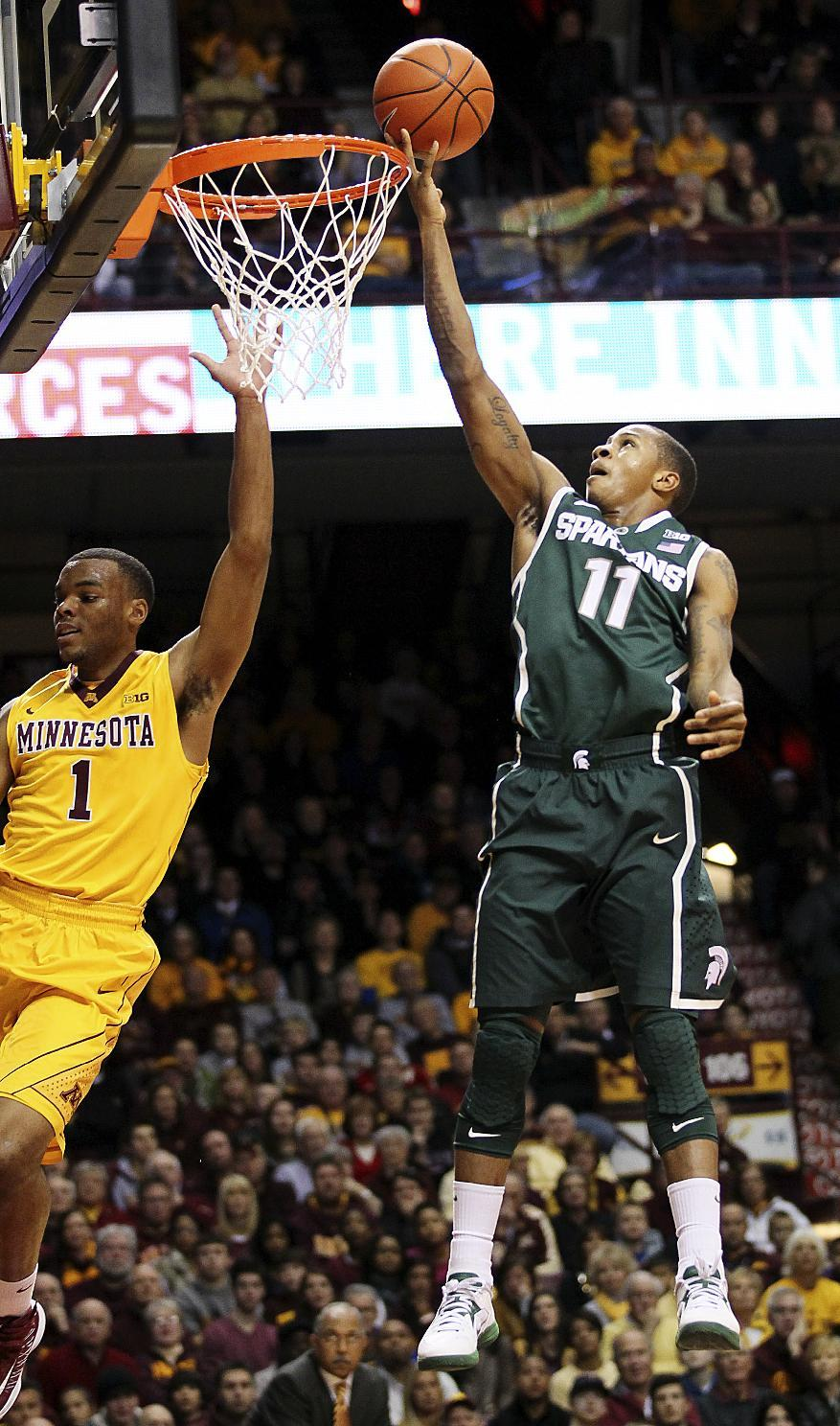 Michigan State guard Keith Appling (11) shoots a layup in front of Minnesota guard Andre Hollins (1) in the first half of their NCAA college basketball game, Monday, Dec. 31, 2012, in Minneapolis. (AP Photo/Andy Clayton King)