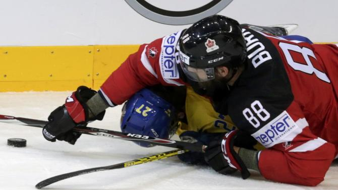 Canada's Burns falls over Sweden's Ericsson during their Ice Hockey World Championship game at the O2 arena in Prague