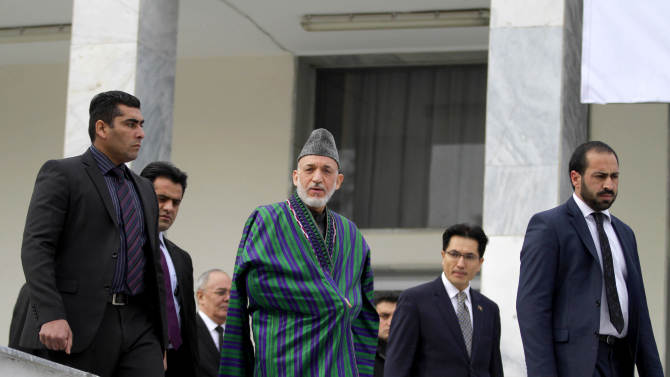 Afghan President Hamid Karzai, center, arrives for a group photo for an ambassadors and consuls general conference in Kabul, Afghanistan, Saturday, Dec. 15, 2012. Afghan President Hamid Karzai said Saturday that the U.S. and NATO troops transferring security to Afghan forces should leave Afghan villages as soon as possible and pull back to their bases. (AP Photo/Ahmad Jamshid)