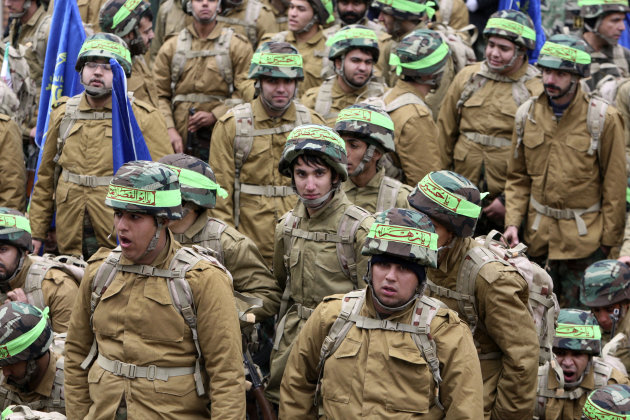 Members of the Iranian paramilitary Basij force, affiliated with the Revolutionary Guard, attend a rally in front of the former US Embassy in Tehran, Iran, Friday, Nov. 25, 2011. Militant Iranian students seized the embassy on Nov. 4, 1979, believing the embassy to be a center of plots against Iran, and then held 52 Americans hostage for 444 days. The US severed diplomatic ties in response, and the two countries have not had formal relations since. The men's headbands bear the names of Shiite saints, including Hussein.(AP Photo/Vahid Salemi)