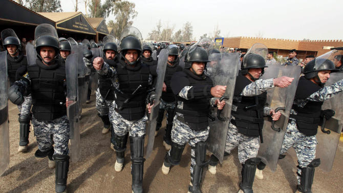 In this Jan. 8, 2012 file photograph, Iraqi riot police march during a graduation ceremony in Baghdad. A report by the U.S. Special Inspector General for Iraq Reconstruction, to be released Monday, July 30, 2012, found that the American Embassy in Baghdad never got a written commitment for Iraq to participate in what initially was envisioned as a five-year, multibillion-dollar effort to train security forces after the U.S. military left last December. (AP Photo/Hadi Mizban, File)