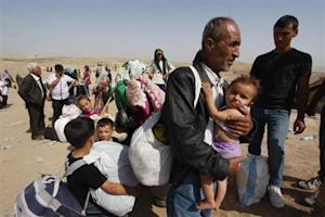 Syrian refugees, fleeing the violence in their country, cross the border into the autonomous Kurdish region of northern Iraq