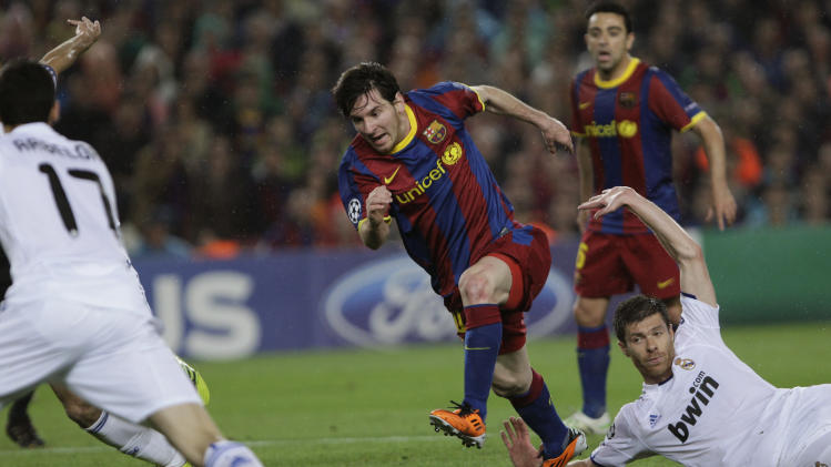 FC Barcelona's Lionel Messi from Argentina, left, runs for the ball next to Real Madrid's, Xabi Alonso, right, during a semifinal, second leg Champions League soccer match at the Nou Camp stadium in Barcelona, Spain, Tuesday  May 3, 2011. (AP Photo/Emilio Morenatti)