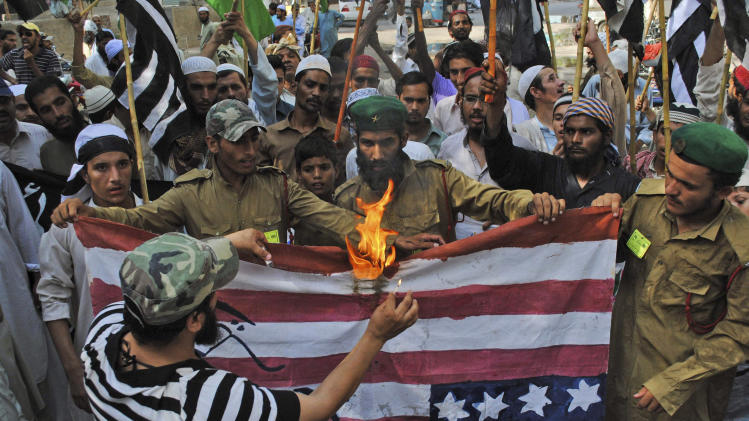 Supporters of Pakistani religious party Jamiat Ulema-e-Islam, burn a representation of a US flag during a rally condemning US drone strikes in tribal areas and the reopening of the NATO supply line to neighboring Afghanistan, in Hyderabad, Pakistan, Friday, June 15, 2012. (AP Photo/Pervez Masih)