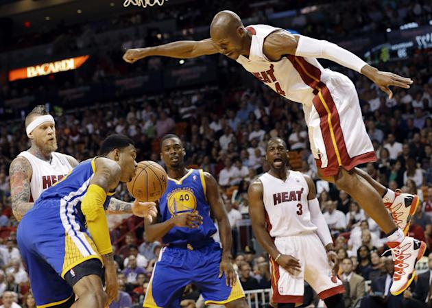 Miami Heat's Ray Allen, right, is fouled after shooting a basket during the first half of an NBA basketball game against the Golden State Warriors, Thursday, Jan. 2, 2014, in Miami. Also shown are