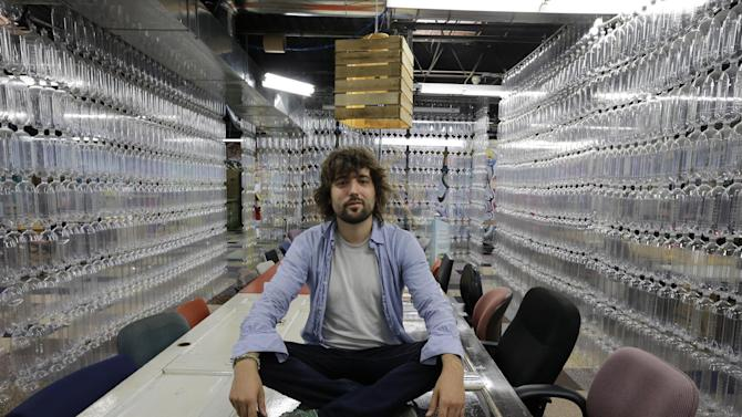 """TerraCycle Inc. founder Tom Szaky sits on a table made from old doors in a meeting room with walls of recycled soda bottles at the company Tuesday, Aug. 5, 2014, in Trenton, N.J. Founded in 2001 by then-20-year-old Princeton student Szaky, TerraCycle works to collect and transform a range of hard-to-recyle items, from potato chip bags to cigarette butts, into colorful consumer products. A new reality show launching Aug. 8 will focus on the New Jersey-based recycling company. The reality docu-drama called """"Human Resources,"""" chronicles what it's like to work at the Trenton-based company. (AP Photo/Mel Evans)"""