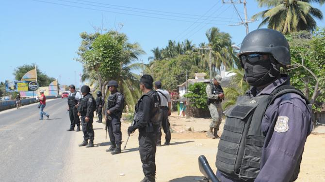 State police stand at a roadblock due to stepped up security after masked armed men broke into a beach home, raping six Spanish tourists who had rented the house in Acapulco, Mexico, Tuesday Feb. 5, 2013. According to the mayor of Acapulco, five masked men burst into a house the Spaniards had rented on the outskirts of Acapulco, in a low-key area near the beach, and held a group of six Spanish men and one Mexican woman at gunpoint, while they raped the Spanish women before dawn on Monday. (AP Photo/Bernandino Hernandez)