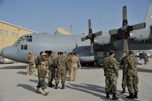 Members of the US and Afghan air forces stand alongside …