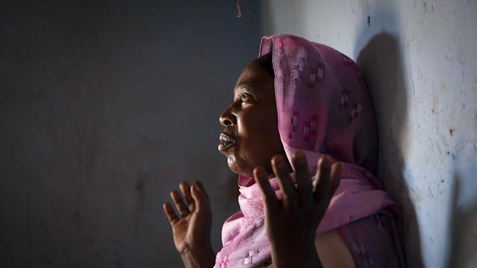 In this photo taken Monday, April 15, 2013, Hamida Kabagwira, a Hutu refugee who was recently reunited with her husband Shaban Mutabazi, (not pictured), says she won't be forced to return to Rwanda, speaking to an Associated Press reporter at her home in the Nakivale refugee camp in Uganda. Nearly two decades after the Rwandan genocide, thousands of refugees living in the camp in Uganda say they fear being forced to return to their home country. (AP Photo/Rebecca Vassie)