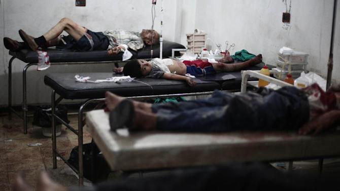 Wounded patients lie are treated at a makeshift hospital following reported shelling by Syrian government forces in the rebel-held city of Douma, northeast of Damascus, on July 30, 2014
