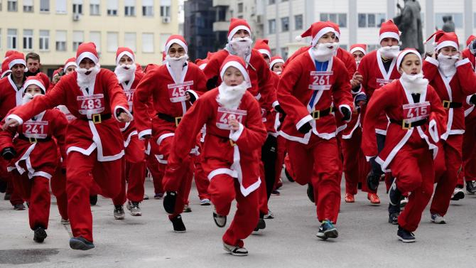 People dressed as Santa Claus race during a competition in Skopje