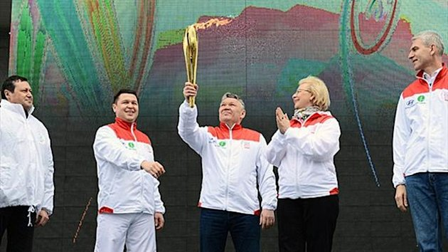 Rafis Burganov, Minister of Youth Affairs, Sports and Tourism of the Republic of Tatarstan holds the 27th Summer Universiade Flame torch with Russian Deputy Minister of Sports Natalia Parshikova