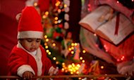 "A young Indian child dressed as Santa Claus plays at a church during Christmas celebrations in Jammu on December 25, 2012. Pope Benedict XVI on Tuesday called for an ""end to the bloodshed"" in conflict-wracked Syria in a traditional Christmas message that touched on several other of the world's conflict zones."