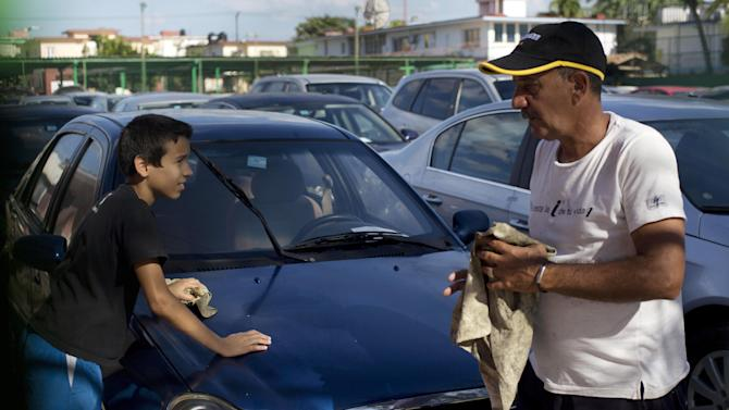 A car dealership worker, right, and a boy clean a used Chinese Geely for sale at a government-run dealership in Havana, Cuba, Thursday, Jan. 2, 2014. This car once was for sale for $5,000 dollars, but the price has risen to as much as $30,000, after a new law took effect eliminating a special permit requirement that has greatly restricted vehicle ownership in the country. (AP Photo/Ramon Espinosa)