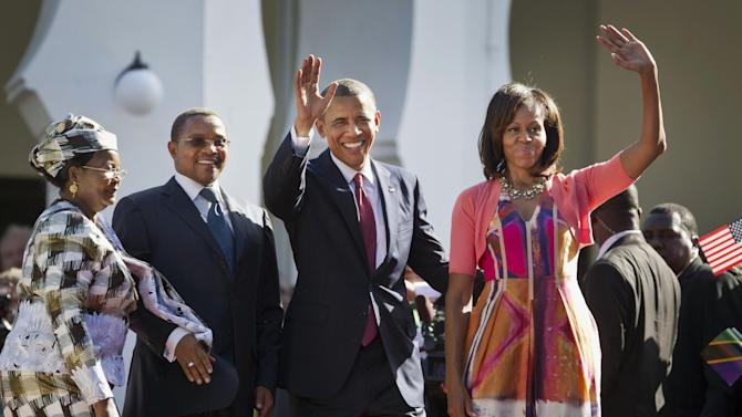 U.S. President Barack Obama, center-right, and first lady Michelle Obama, right, wave as they enter State House accompanied by Tanzanian President Jakaya Kikwete, center-left, and Tanzanian First Lady Salma Kikwete, in Dar es Salaam, Tanzania Monday, July 1, 2013. Teeming crowds and blaring horns welcomed President Barack Obama to Tanzania's largest city, where the U.S. president's likeness is everywhere as he arrived on the last leg of his three-country tour of the African continent. (AP Photo/Ben Curtis)